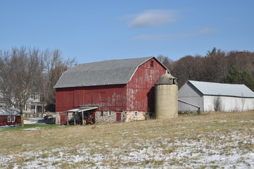 Old red barn in early winter with just a touch of snow on a sunny day on a farm