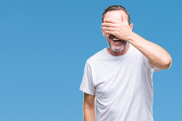 Middle age hoary senior man wearing white t-shirt over isolated background smiling and laughing with hand on face covering eyes for surprise. Blind concept.