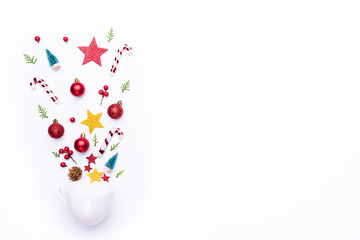 Christmas background concept. Top view of white cup splash out Christmas decoration with gift box spruce branches, pine cones, red berries and bell on white background.