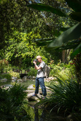 Photographer take photo in the garden. A man standing on stone.