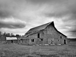 Black and white image of dreary abandoned dilapidated farm barn with cloudy skies in northern Minnesota