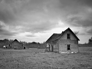 Black and white image of dreary abandoned dilapidated farm house and barn with cloudy skies in northern Minnesota