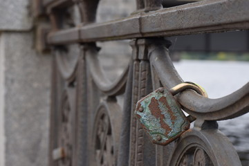 old rusty lock on the metal fence of the bridge. Valentine's day background. Tinting the image. Blurred background.