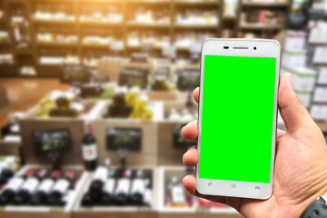 Men use hold smartphone blurred images of Various alcohol bottles in a row at the spirits store background.