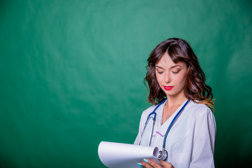 Portrait beautiful female doctor smiling and filling out a medical chart on green background with copy space. Healty and medical concept.Doctor filling prescription on clipboard isolated.Beautiful and