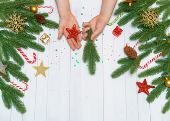 Child hand with toy star and fir tree branch on wooden background decorated christmas accessories.