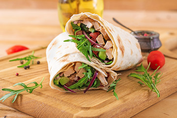 Tortillas wraps with chicken and vegetables on  wooden background. Chicken burrito. Healthy food.