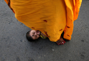A Hindu woman steps over an infant in a ritual seeking blessings for the infant from the Sun god during the religious festival of Chhath Puja in Kolkata