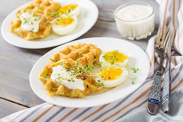 Healthy breakfast or snack. Potato waffles and boiled egg on grey wooden table.