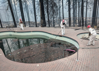 Forensic investigators search a community swimming pool for victims of the Camp Fire in Paradise