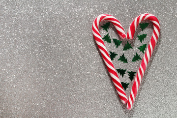 A heart formed with Christmas sticks and confetti as New Year background with copy space
