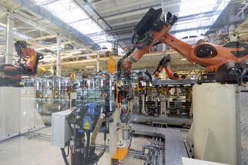 process of welding cars behind glass. Modern Assembly of cars at plant. automated build process of the car body