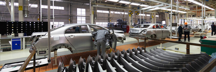 Engineer looks into the cab of the car on the production line. Automotive production line. long format. Wide frame Wall mural