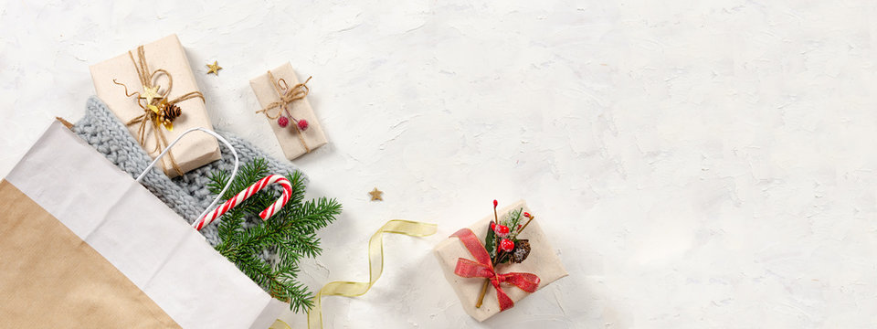 Christmas banner. Winter Holidays sale background. Shopping bag, presents with candy cane, fir branch and golden ribbon. Top view, copy space