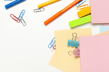 Sticky notes with markers, colored pens, paper clips laying on a table