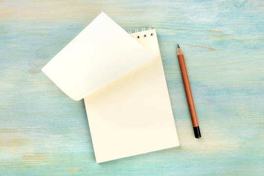 Turn a New Page. An overhead photo of a spiral notepad with a blank sheet of paper, shot from the top on a teal blue background with a pencil and a place for text