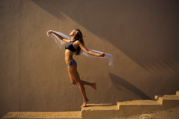 girl in a bathing suit dancing in a beautiful light