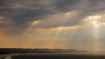 Sun rays through thunder clouds over jeffreys Bay in South Africa