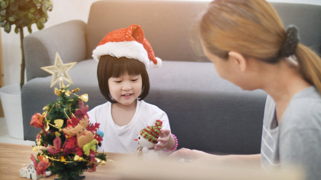 Happy lovely Asian girl decorating ornament on Christmas tree with her mother