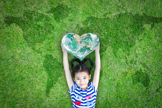 World kindness day concept with happy kid raising heart planet on ecological friendly natural green lawn. Element of the image furnished by NASA