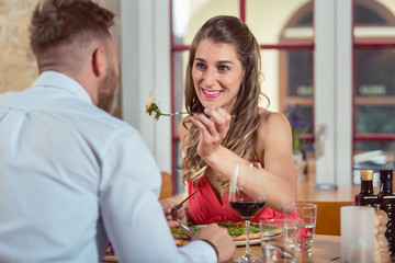 Young woman on date feeding her boyfriend at restaurant