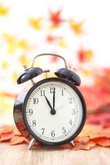 Old clock on autumn leaves