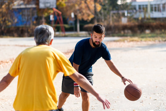 Father and son playing basketball in the park