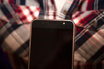 smartphone and checkered female shirt