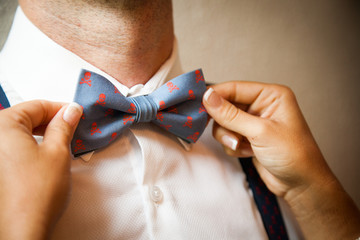 A pair of women's hands attach the bow tie to a man.