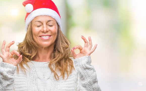 Middle age senior hispanic woman wearing christmas hat over isolated background relax and smiling with eyes closed doing meditation gesture with fingers. Yoga concept.