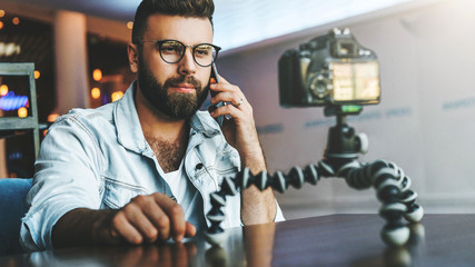 Video blogger in stylish glasses shoots video streaming for users while sitting in coffee shop and talking on cellphone.