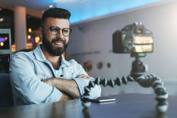 Bearded male video blogger creates video content for his channel. Man vlogger relieves himself on camera with tripod.