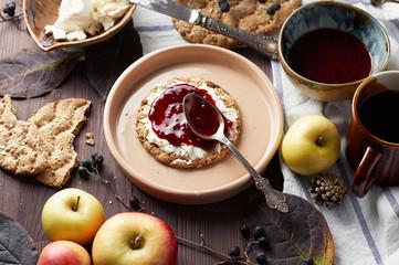 Swedish rye crispbread with cream cheese and raspberry jam. Autumn and winter breakfast concept.