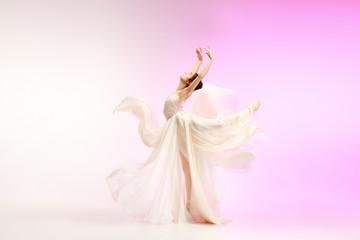 Young graceful female ballet dancer or classic ballerina dancing at pink studio. Caucasian model on...