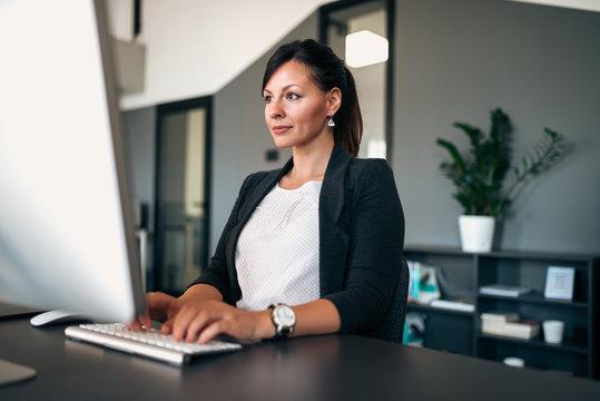 Portrait of beautiful businesswoman working on computer in modern office.