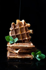 waffles - delicious dessert, breakfast with honey. Photo on a black background. Waffles decorated with mint and sprinkled with honey