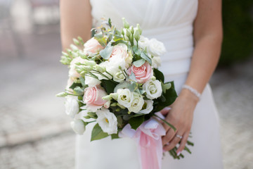 wedding bouquet - pastel flowers in the hands of the bride. Pink, white, cream and jelly kwaites kept by the bride.