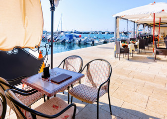 Sidewalk street cafe at Adriatic Sea and Marina of Izola