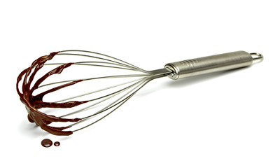 Chocolate immersed whisk isolated on white background