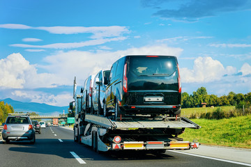 Truck carrier with mini vans on road in Slovenia