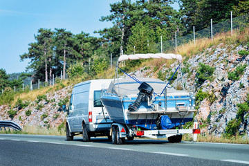 RV Camper Car with motorboat in Road in Slovenia