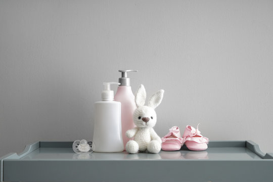 Bunny toy with shoes, pacifier and cosmetics for baby on grey table