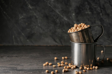 Metal cups with dry chickpeas on dark table