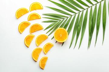 Sliced orange and palm leaf on white background