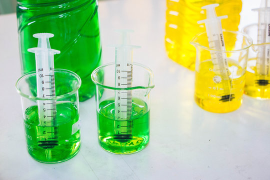 The needle syringe is dipped in green and yellow chemicals in the beaker to prepare a scientific experiment.
