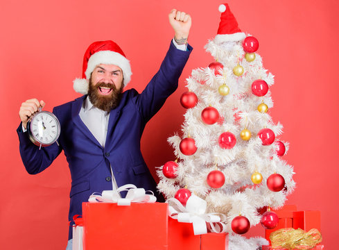 Counting time till christmas. How much time left. Keep track of time. Time to celebrate. Man bearded wear suit and santa hat hold clock. Businessman join christmas celebration. Last minute deals