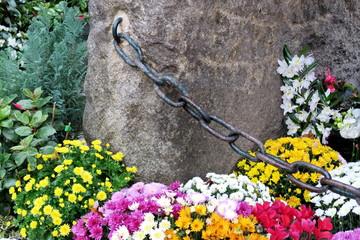 tombeau en pierre fleuri avec chrysanthèmes colorés et chaîne de fer
