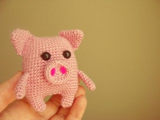 The little pig is crocheted in the hands of man