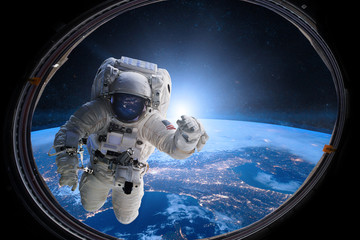 Astronaut in outer space from porthole on background of the Earth. Elements of this image furnished by NASA.