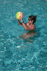 Woman playing with a ball in the swimming pool - copy space.